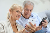 Couple at home using smartphone — Stock Photo