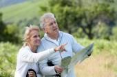 Senior hikers reading orientation map — Stock Photo
