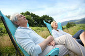 Couple relaxing in folding chairs — Stock Photo