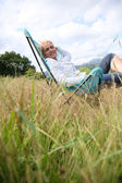 Woman relaxing in chair in countryside — Stock Photo