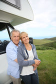 Couple standing by motorhome in countryside — Stock Photo