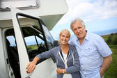 Couple standing in front of camping car — Stock Photo
