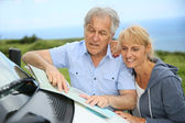 Senior people reading road map — Stock Photo