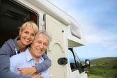 Senior couple standing by camper door — Stock Photo
