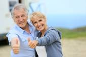 Couple standing by camper on road stop — Stock Photo