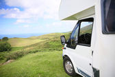 Camper parked on hill by sea — Stock Photo