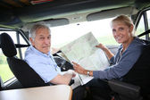 Сouple riding camper and reading map — Stock Photo