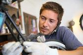 Hombre que trabaja en el taller de bicicletas — Foto de Stock