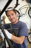 Man working in bike rental shop — Stock Photo