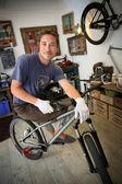 Smiling craftsman in bike workshop — Stock Photo