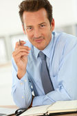 Businessman in office writing on agenda — Stock Photo