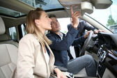 Car dealer showing vehicle to clients — Stockfoto