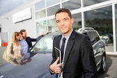 Smiling car dealer standing by vehicle — Stock Photo