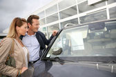 Couple in car dealership — Stock Photo