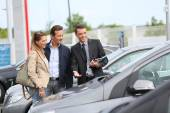 Car dealer showing vehicles to couple — Stock Photo
