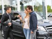 Salesman giving keys to clients — Stock Photo