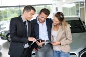 Couple in car dealership looking at brochure — Stock Photo