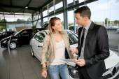 Car dealer showing vehicle to woman — Stock Photo
