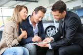 Couple signing car purchase order — Stock Photo