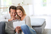 Couple websurfing with tablet at home — Stock Photo