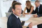 Corporate man sitting at meeting table — Stock Photo