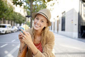 Shopping girl using smartphone in town — Stock Photo