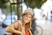 Smiling woman sitting on public bench — Stock Photo