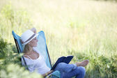 Woman reading book in outdoor chair — Stock Photo