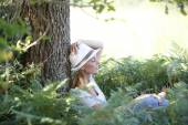 Woman with hat relaxing in forest — Stock Photo