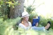Woman in park enjoying novel — Stock Photo