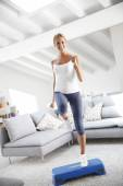 Woman doing fitness exercises in front of TV — Stock Photo