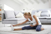 Woman at home stretching out — Stock Photo