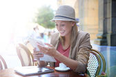 Girl in coffee shop reading newspaper — Stock Photo