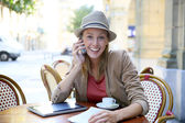 Girl in coffee shop talking on phone — Stock Photo