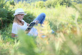 Woman reading book in countryside — Stock Photo