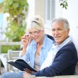 Senior couple reading book outside — Stock Photo #58084849