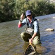 Fisherman catching fario trout in river — Stock Photo #58085089