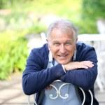 Senior man sitting in home garden — Stock Photo #58085581