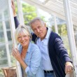 Couple standing by greenhouse in garden — Stock Photo #58085887