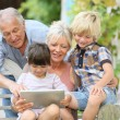 Grandparents playing on tablet with kids — Stock Photo #58086255