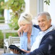 Senior couple reading book outside — Stock Photo #58087983