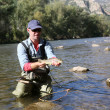 Fisherman catching fario trout in river — Stock Photo #58089485