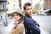 Couple in street leaning back to back — Stock Photo