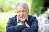 Senior man sitting in home garden — Stock Photo