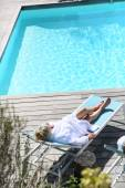 Woman relaxing by pool — Stock Photo