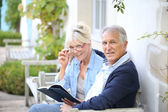 Senior couple reading book outside — Stock Photo