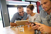 Students in campus lounge websurfing on tablet — Stock Photo