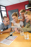 Friends in campus lounge websurfing with tablet — Foto de Stock