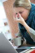 Woman working at home and being sick — Stock Photo
