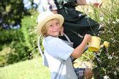 Little boy watering flowers in garden — Stock Photo